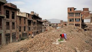 A woman dries vegetables on the rubble of a building damaged in the April 2015 earthquake in Bhaktapur