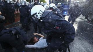 Joven manifestante siendo detenido por la policía.
