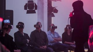 People listen to a singer while wearing virtual reality handsets