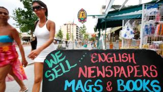 "women in beach clothes walking past a sign that reads ""We sell English newspapers mags and books"""