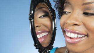 Foto de mujer mirándose al espejo