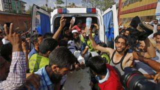 Volunteers carry an injured man from an ambulance outside a hospital who was shot during clashes between security forces and protesters in Srinagar on July 11, 2016.