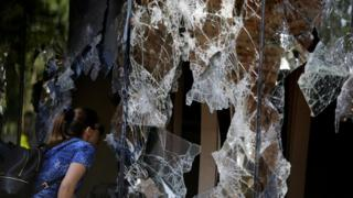 A woman looks through damaged windows of the Congress building a day after a demonstration against a possible change in law to allow for presidential re-election in Asuncion, Paraguay, April 1, 2017