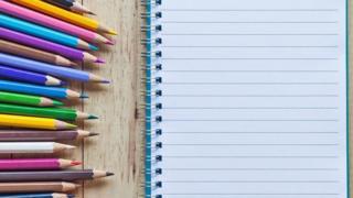 Un cuaderno con una hoja en blanco y creyones