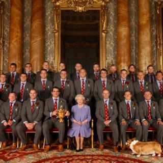 Queen Elizabeth II, and Berry the corgi, with the England rugby squad, at a reception at Buckingham Palace in London to celebrate winning the Rugby World Cup.