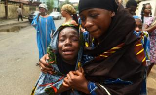 A young girl is comforted as she cries during a dramatisation of the crucifixion of Jesus Christ to mark Good Friday, heralding the start of Easter celebrations, in Lagos on March 30, 2018