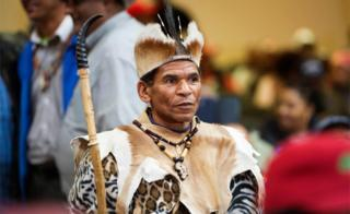 A man in traditional Khoi San regalia waits before a land expropriation hearing being held in a church in Cape Town - Friday 4 August 2018