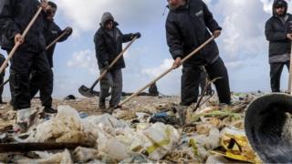 Orang-orang membersihkan pantai.