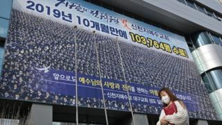 A woman wearing a face mask walks in front of the Daegu branch of the Shincheonji Church of Jesus, 27 February 2020