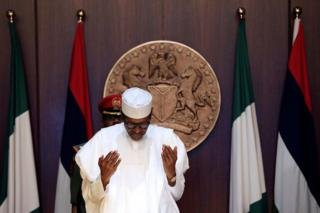 "Nigeria""s President Muhammadu Buhari is seen prayi"