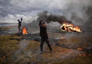 Un jeune lance un pneu en feu