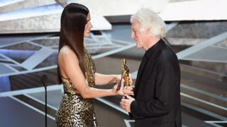 Cinematographer Roger A. Deakins (R) accepts Best Cinematography for 'Blade Runner 2049' from actor Sandra Bullock onstage during the 90th Annual Academy Awards