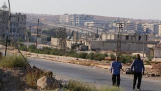 People walk near the Castello Road in Aleppo (14 September 2016)