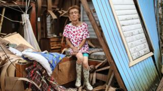 Hurricane victim sits in damaged home