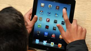 person using an Apple iPad tablet