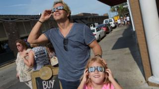Nikos Spyridonos and his daughter Zoe try out eclipse glasses ahead of the total solar eclipse in Charleston, South Carolina, on August 20, 2017.