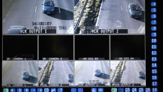 A television monitor shows the results of CCTV camera and infra-red vehicle number plate recognition cameras, tracking vehicles travelling on the M62 motorway in Cheshire