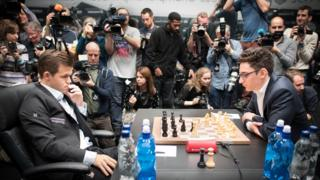 Magnus Carlsen (left) and challenger Fabiano Caruana face each other over a chess board while a host of photographers clamber in the background