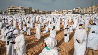Followers of the Layene community wearing protective masks take place on the beach in front of the Yoff Layene Mosque, during the Islamic festivity of Korite in Dakar, Senegal, on May 24, 2020,