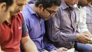 Hombres sentados concentrados en ver sus teléfonos
