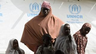 Nigerian refugees wait outside a tent of UNHCR, on April 7, 2015 in the Nigerian refugees camp named 'Dar-es-Salam' near Baga Sola in the Chad lake region.