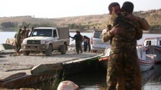 Tabka Barajı kıyısında sevinçle birbirlerine sarılan iki SDG askeri