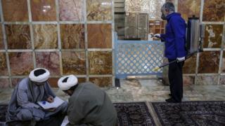 A man sprays disinfectant to prevent the spread of coronavirus and two men sit on the floor reading in the Fatima Masumeh Shrine in Iran