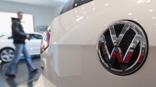 A visitor looks at a VW car in a Berlin showroom in 2013