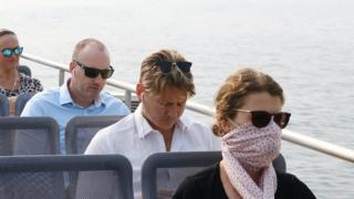 A woman wears sunglasses and a scarf while travelling on a Sydney ferry during a smoke haze across the city