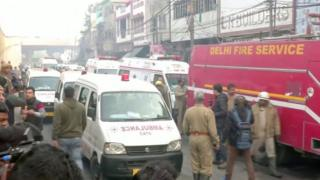 Ambulances and firefighters at the scene of the fire in Delhi