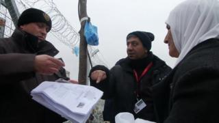 Border guards check a woman's papers