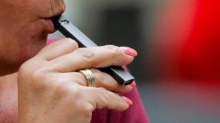 A woman vapes a JUUL