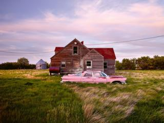 in_pictures An abandoned pink car in front of a wooden house