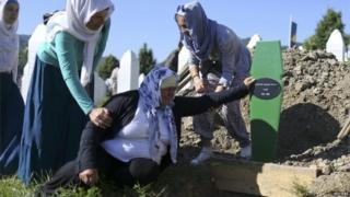 An elderly woman is comforted as she cries at an open grave in Memorial Centre in Potocari, near Srebrenica. File photo