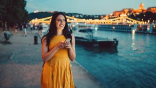 Young woman with a phone in her hand. She's smiling, wearing a yellow dress and walking by the river in Budapest at dusk.