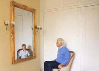 A man looks at a reflection of his younger self in the mirror