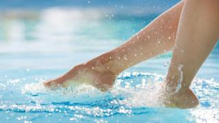 Woman's feet above surface of swimming pool