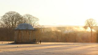 Frosty parkland. Two dogwalkers can be seen by a bandstand