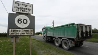 A lorry driving past a sign that reads: Welcome to Northern Ireland