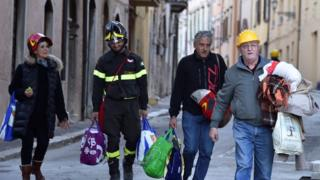 Firefighters help people find safety in Norcia in Italy
