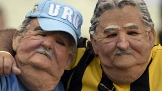 Dos personas con la máscara de Mujica.