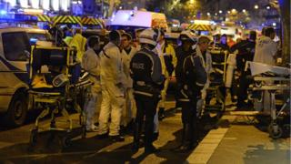 Rescuers and police stand by on Boulevard des Filles du Calvaire near the Bataclan concert hall in central Paris