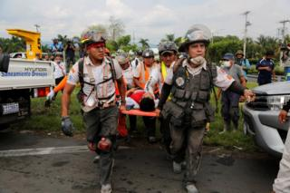 Firefighters carry a man on a stretcher near an area affected by the eruption