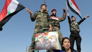 ทหารและประชาชนซีเรียโบกธงชาติและชูภาพของประธานาธิบดีบาร์ชา อัล อัสซาด