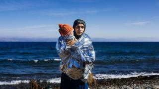 A woman holds her child wrapped in an emergency blanket shortly after arriving with other migrants and refugees on the Greek island of Lesbos