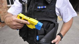 File photo from 2009 of an Avon and Somerset police officer holstering a Taser X26 during training