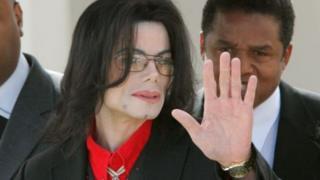 """Майкл Джексон залишає будівлю окружного суду Санта-Барбари під час процесу за звинуваченням у розбещенні 13-річного Гевіна Арвізо у себе на ранчо """"Неверленд"""" в 2003 році. Фото 24 березня 2005 року."""