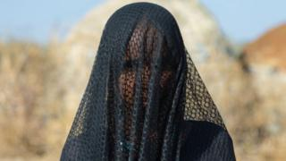 Ethiopia woman cover her face wit veil sake of dust