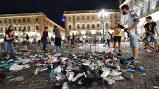 """حقائب وأحذية على الأرض في موقع التدافع في ميدان """"بياتسا سان كارلو"""""""