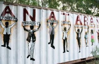 Figures painted holding signs saying 'Poverty. Tribalism. Violence. Hunger. Corruption. Oppression. Injustice. Ignorance'.